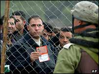 Palestinians show their ID papers to Israeli soldiers as they wait to cross the Hawara checkpoint on their way out of the West Bank town of Nablus