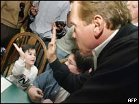 Schwarzenegger with a child during a four-day campaign for his budget plan