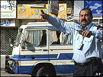 A Baghdad police man clears the scene around the bus