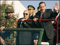 Turkish PM Recep Tayyip Erdogan waves while parading with Turkish Cypriot leader Rauf Denktash, left, during ceremonies in November marking the 20th anniversary of the breakaway TRNC
