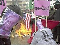 Palestinian demonstrators in Nablus burn an American flag behind effigies of Geneva Accord signatories Yasser Abed Rabbo (left) and Yossi Beilin