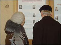 Voters look at posters in a polling station