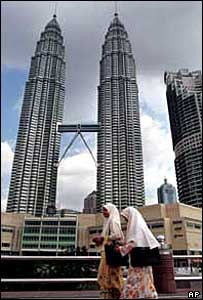 Young people walk past Kuala Lumpar's Petronas Towers