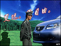 Policeman walks past car advertising poster