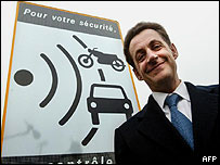 French Interior Minister Nicolas Sarkozy posing in front of a speed control sign during the inauguration of the first automatic speed detecting radar.