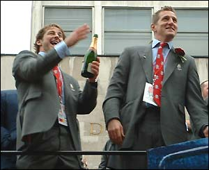Andy Gomarsall and Will Greenwood crack open the champagne on the bus, watched by Dominic Smith