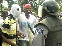 Protesters and a policeman in Port-au-Prince on Thursday