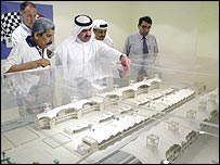 Sheikh Fawaz bin Mohammed (centre), the president of the Bahrain Racing Circuit Company, shows off a model of the Middle Eastern country's new F1 track