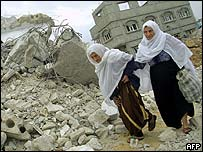 Palestinian women walk amid the rubble of a house demolished by the Israeli army in the Gaza Strip