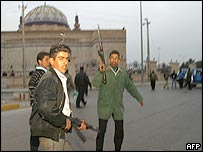 Armed pro-Saddam Hussein Iraqi youths clash with Iraqi police in the Azamiyah district of Baghdad after a rally in support of the Iraqi former leader on 15 December