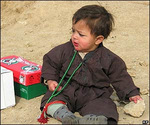 Afghan baby holds a rock in a Kabul refugee camp as he sits by a box carrying toys donated by Canadian soldiers