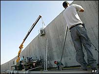 Israeli technicians install surveillance cameras on West Bank barrier