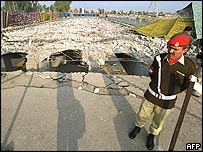 A guard stands near a bridge destroyed in the attempt on Musharraf's life