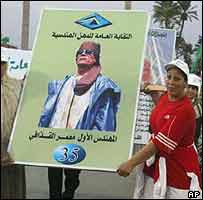 Libyan women carry placard praising Gaddafi on 35th anniversary of his rule, September 2003