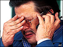 Former Philippines President Joseph Estrada speaking on a telephone