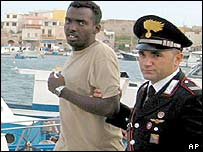 Italian coast guard with a rescued migrant