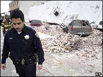 Police officer walks away from the remains of a two-story building following an earthquake in Paso Robles, California