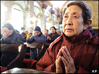 A Chinese woman prays at the government-approved Nantang Catholic Cathedral in Beijing
