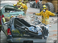 Rescue workers remove masonry and bricks from crushed cars in Paso Robles
