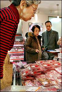 Japanese shoppers inspect beef in a shop