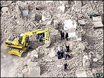 A bulldozer digs for bodies in Bam