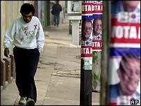 A pedestrian walks in front of election campaign posters of Oscar Berger, in Guatemala City