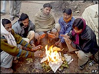 Men warming their hands at a roadside bonfire