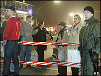 Armed policeman [right] and residents stand by roadblock at military hospital in Wansbeck, Germany