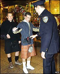 New York detective Rich Turk uses a portable metal detector on Scotland's Darren McAllister (centre) and Mark Chisholm (left) at a checkpoint in Times Square