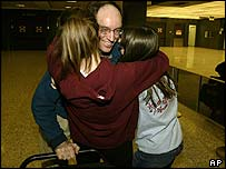 Michael Duell is greeted by his daughters after he and the other BA 223 passengers are allowed to disembark