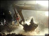 Iranian rescue workers watch a digger at work in the ruins of a house