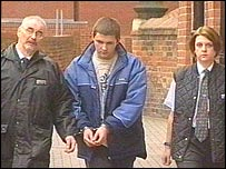 Paul Smith (middle) flanked by prison officers