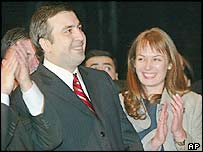Mikhail Saakashvili (left) smiles while listening to the preliminary election results as his wife Sandra Roelofs applauds him in Georgia's capital Tbilisi