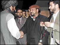 Delegates shake hands at the closing ceremony of the loya jirga