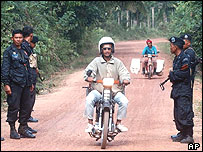 Thai-muslim villagers ride their motorcycles past a checkpoint of Thai rangers in Narathiwat
