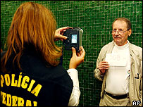 US citizen is photographed by a Brazilian immigration officer at Brazil's Guarulhos International airport in Sao Paulo