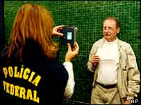 An American citizen has his picture taken by a Brazilian immigration officer, Sao Paulo,  5 January 2004