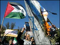 Iranians wave a Palestinian flag while burning an Israeli flag