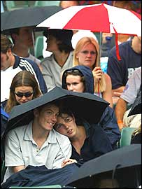 Tennis fans at Wimbledon shelter under umbrellas
