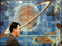 Житель Китая рядом с мозаикой с изображением Луны