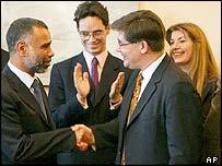 Libyan representative Saleh Abdul Salam (left) shakes hands with families' representative Guillaume Denoix de Saint-Marc