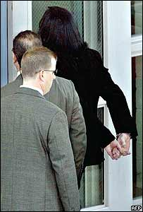 Michael Jackson being led into police station in handcuffs