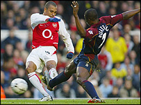 Gilberto Silva tries to shoot as George Boateng gets in a challenge