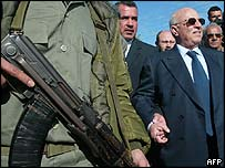 Mr Qurei with armed guard at the Israeli wall