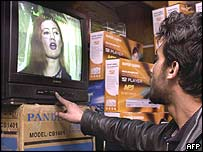Afghan man watches woman singing on TV