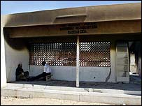 Two people sit at the entrance of a burnt out police station