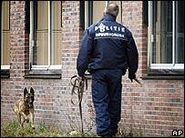 Un policía utiliza un perro entrenado para buscar al atacante.