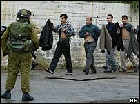 An Israeli army officer looks on as Palestinian workers lift their clothes to show him they are not carrying explosives, Erez border crossing