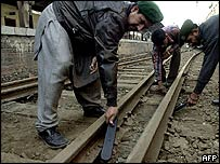 Security personnel checking railway tracks