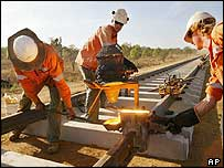 Workers check a joint on Alice Springs to Darwin railway line near Adelaide River
